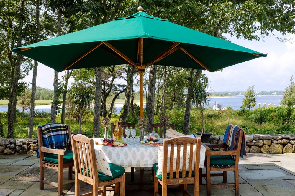 Outdoor patio with umbrella covered table set for tea