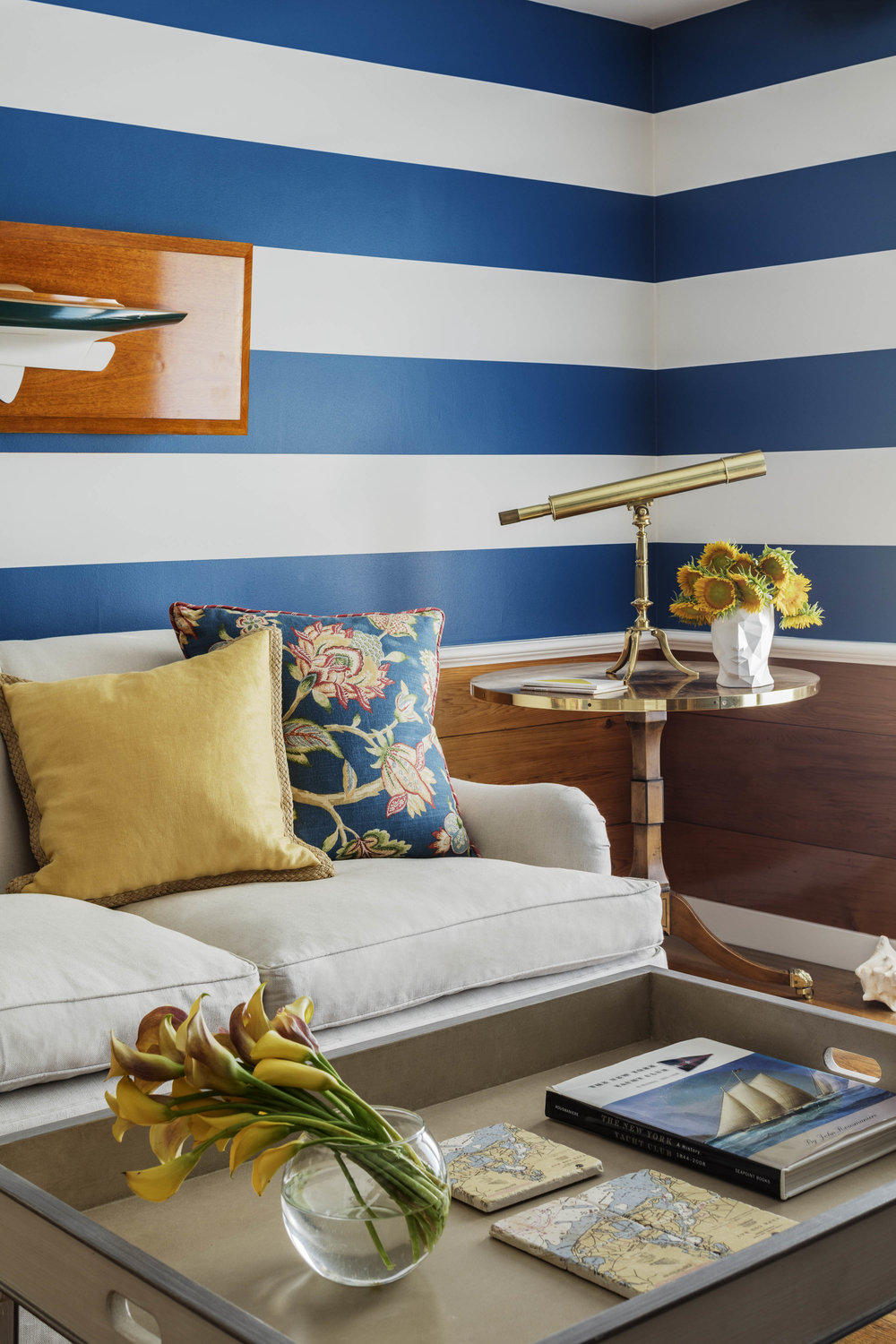 Sitting area with blue and white striped walls and classic looking glass on side table