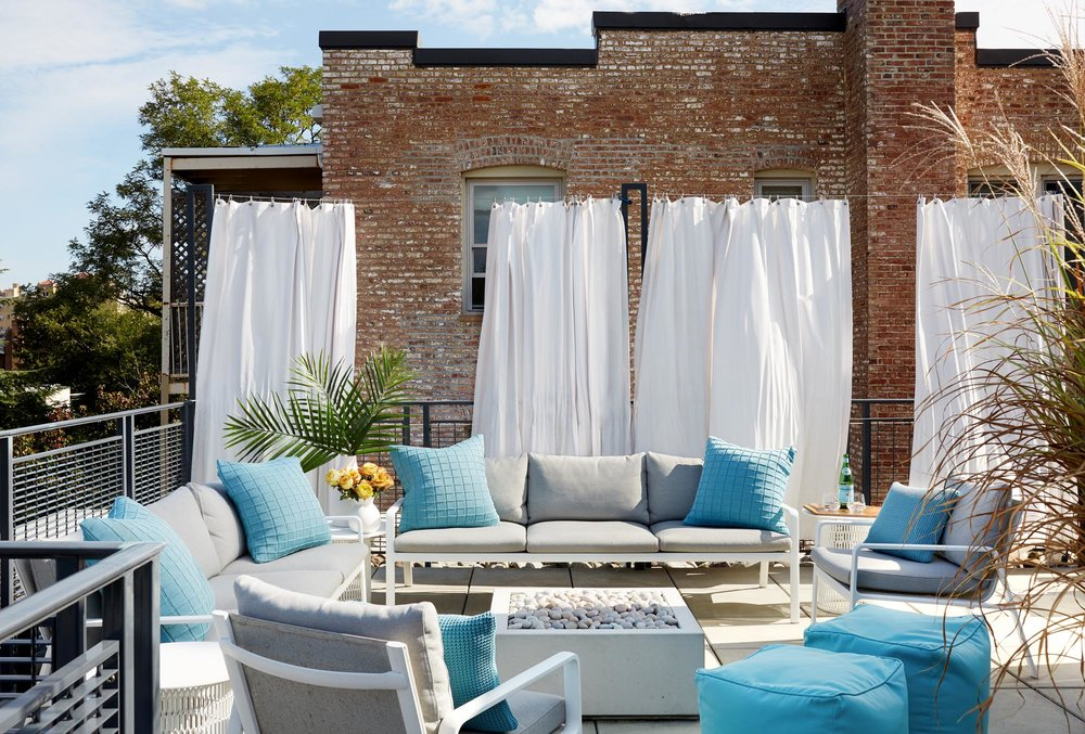 Outdoor rooftop patio with light furnishings and white sheets hung for discreetness