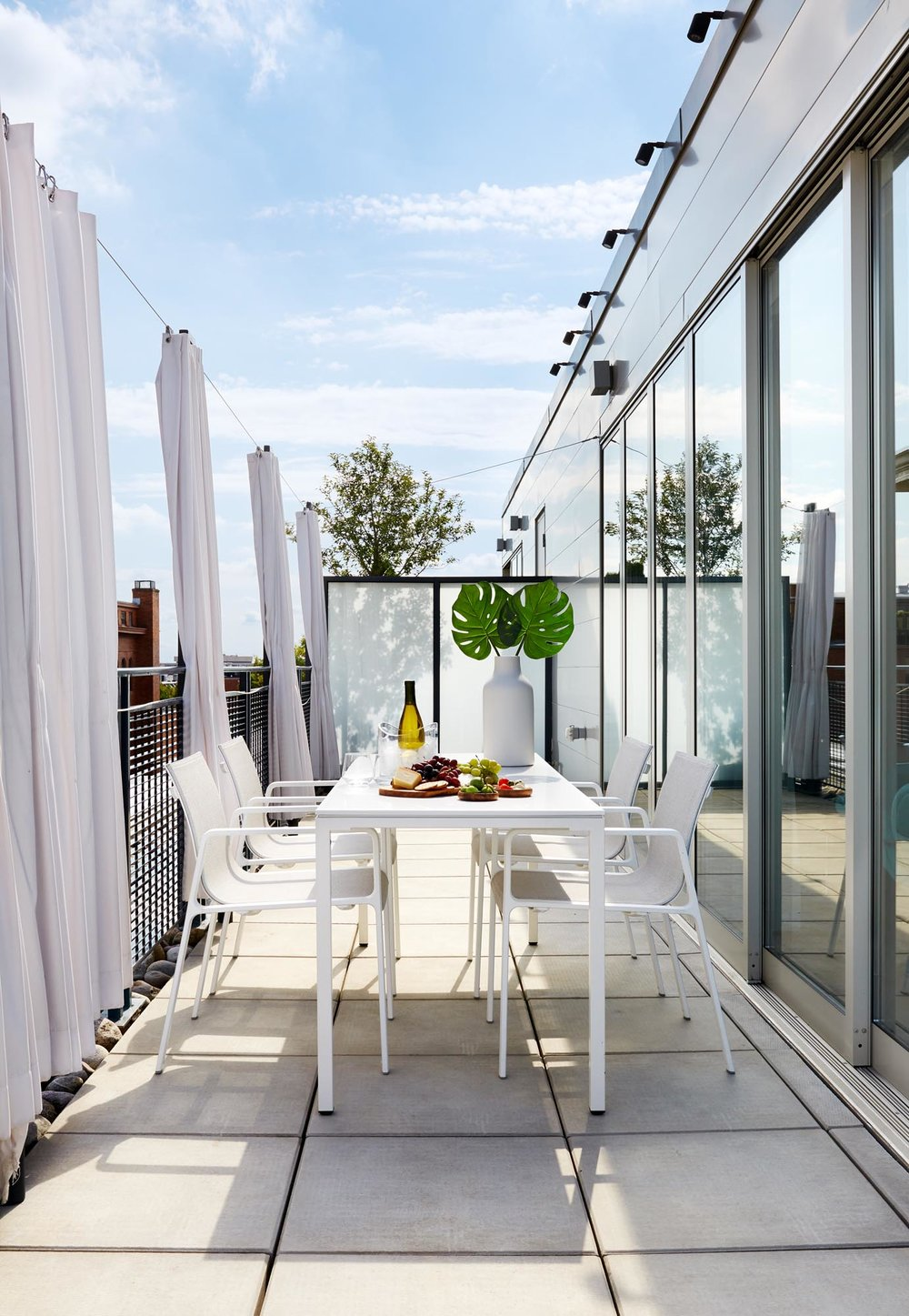 Bright outdoor patio with white tables and chairs