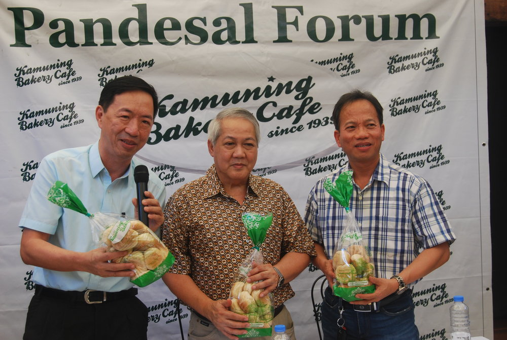 Flores, Casiple, and Bravo show off Kamuning Bakery's famous pan de sal after the forum
