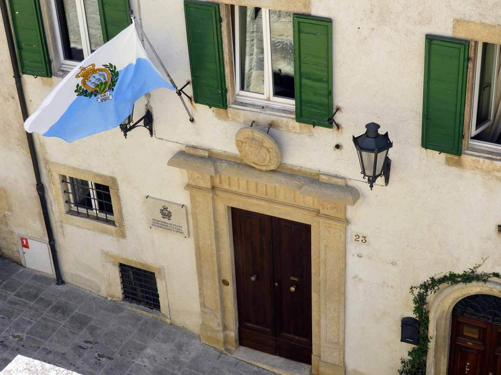san-marino-micro-nation-flag-green-shutters-wood-door-stone.jpg