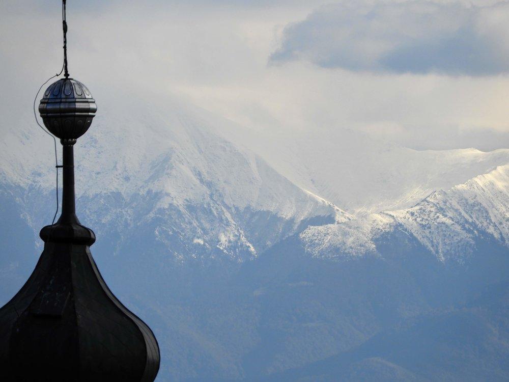 romania-sibiu-church-steeple-snow-mountains-autumn.JPG