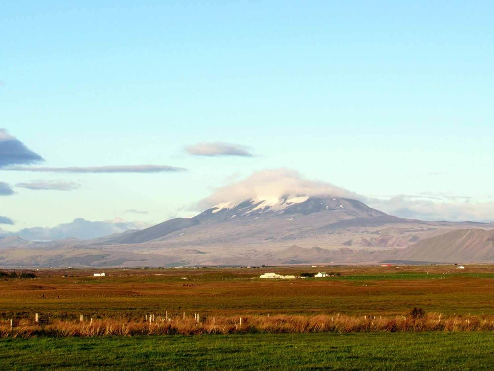 """Hekla Volcano - Iceland's most active volcano, known by locals as """"Gateway to Hell"""". Etymology. The word Hekla means """"short hooded cloak"""". Perhaps it alludes to (or is inspired by) the frequent cloud looming over its upper ridge line. It is possible to hike to the summit, but we had an entire ring road to get around and just over a week to do it. So, we opted to admire it from afar. Maybe next time, Hekla."""