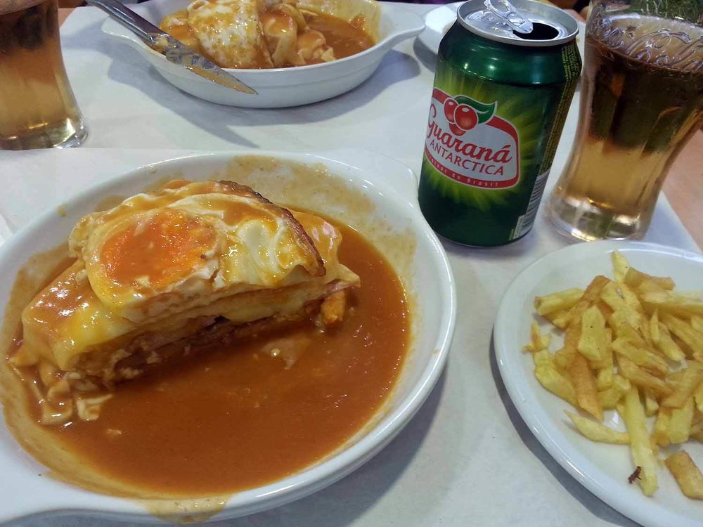 "Eat Francesinhas! - Oh, how we LOVE Francesinhas.  This typical Portuguese sandwich was born in the city of Porto when chef, Daniel da Silva, traveled to France to work and after returning, adapted the French croque-monsieur sandwiches to appeal to the locals. A Francesinha, meaning ""Little French Girl"" consists of thinly sliced wet-cured ham (linguiça), fresh sausage (chipolata), and steak sandwiched between two slices of bread. It's covered in a mild melted cheese, topped with a fried egg, and is finally smothered in a delicious hot, tomato sauce. It's basically a meat-lover's grilled cheese sandwich on steroids. Be sure to eat it with some Guarana (fruit soda) and  french fries. These probably have more calories than is needed for a whole day and they aren't healthy whatsoever, but they are awesome (and cheap - you can usually get the sandwich, drink and fries for about 5 euro)! One of our favorite spots to indulge is Cafe Dragao, but you can find them just about anywhere in Porto. We were once lucky enough to find them at a Portuguese restaurant in Romania. It hit the spot!"