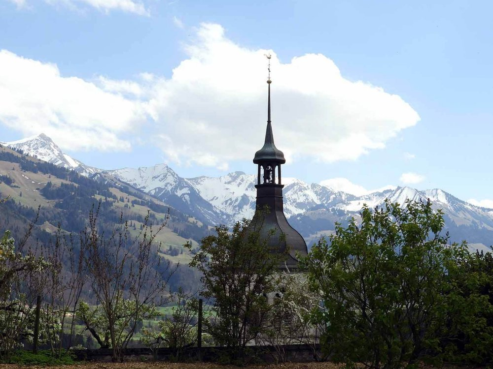 switzerland-gruyeres-steeple-roof-mountains.JPG