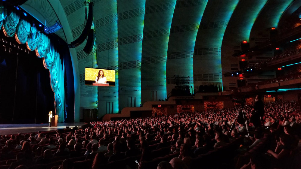 Sheela keynotes the AIA conference at Radio City Music Hall.