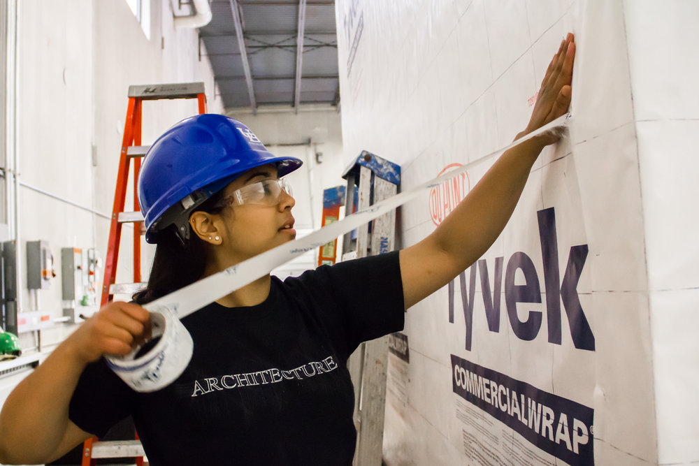 Pooja Bhatt, a University at Buffalo architecture graduate student, helping to construct the GRoW Home, the school's entry in the 2015 U.S. Department of Energy's Solar Decathlon. Photograph by Zhi Ting.