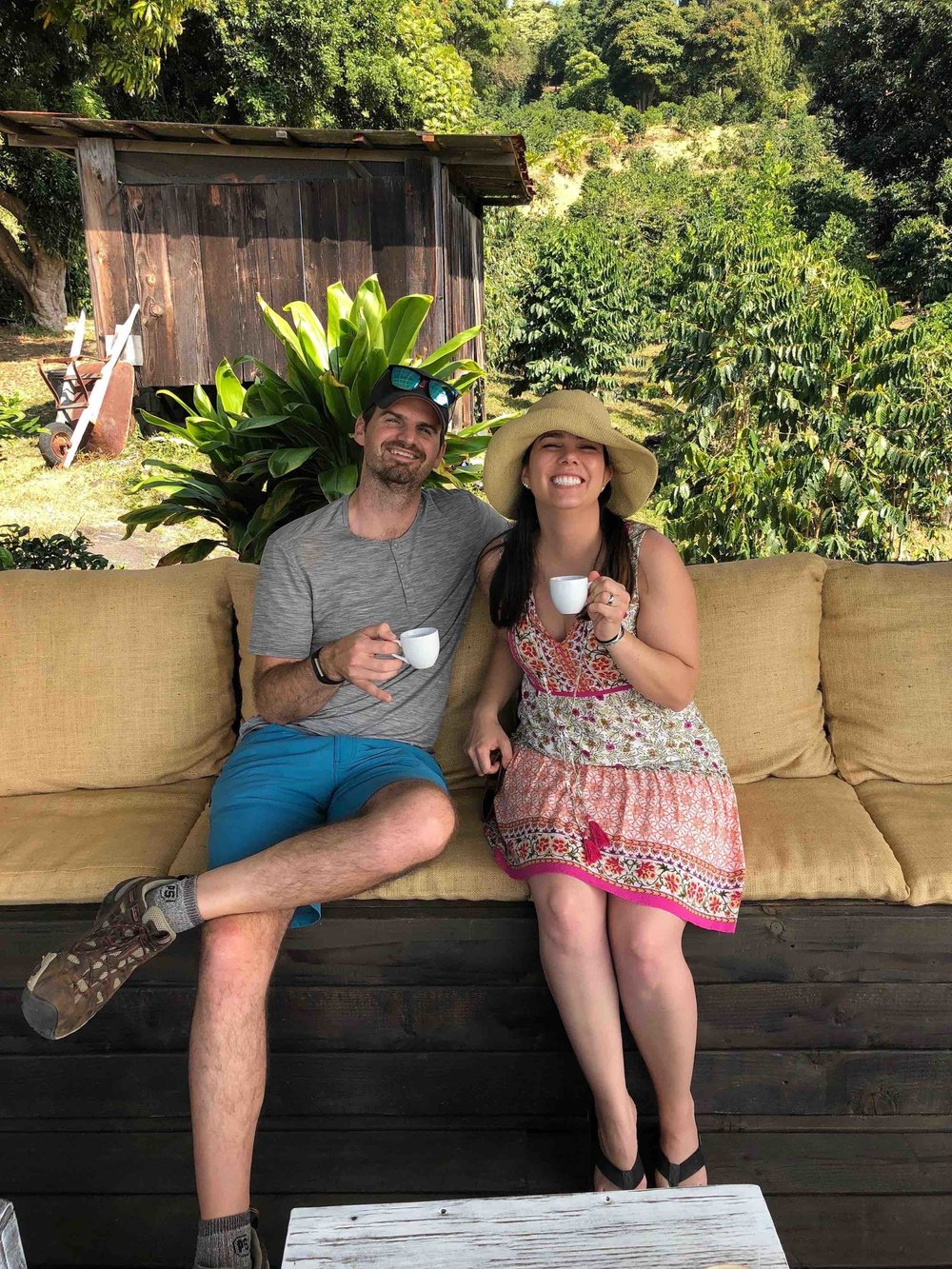 Couple enjoys Kona coffee tasting at Hala Tree in Kona, Hawaii.