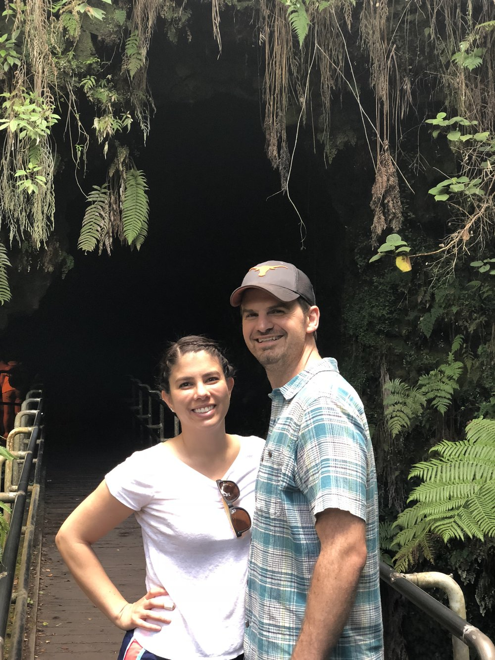 Couple pose for a photo before entering a lava tube at Volcanos National Park.