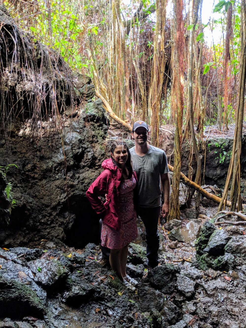 Couple stand inside a lava tube that has a small opening just off the road to Hana.
