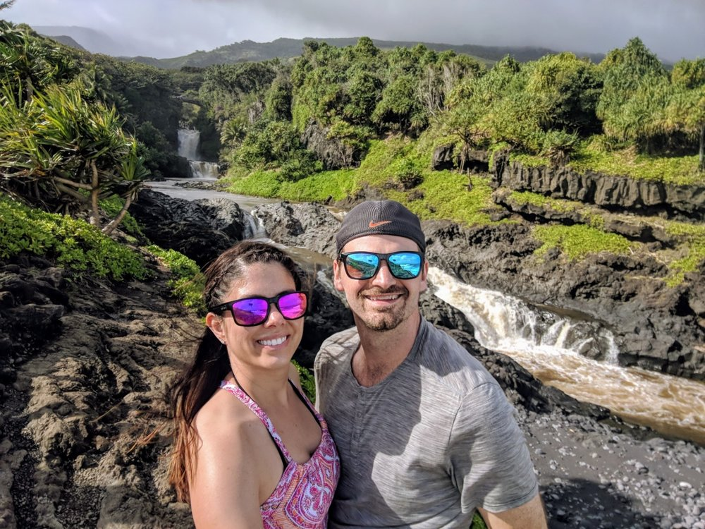 Couple stand in front of the 'Seven Sacred Pools' on the road to Hana, Maui.