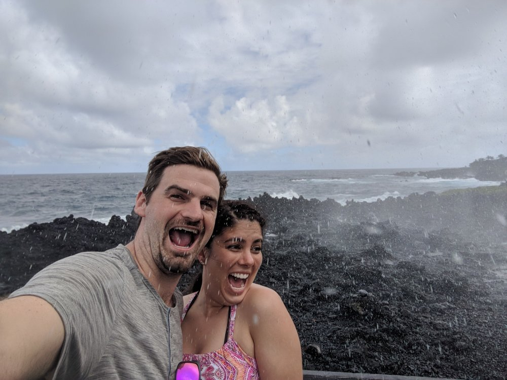couple pose for a selfie in front of blow hold at the Wai'napanapa State Park, Maui.