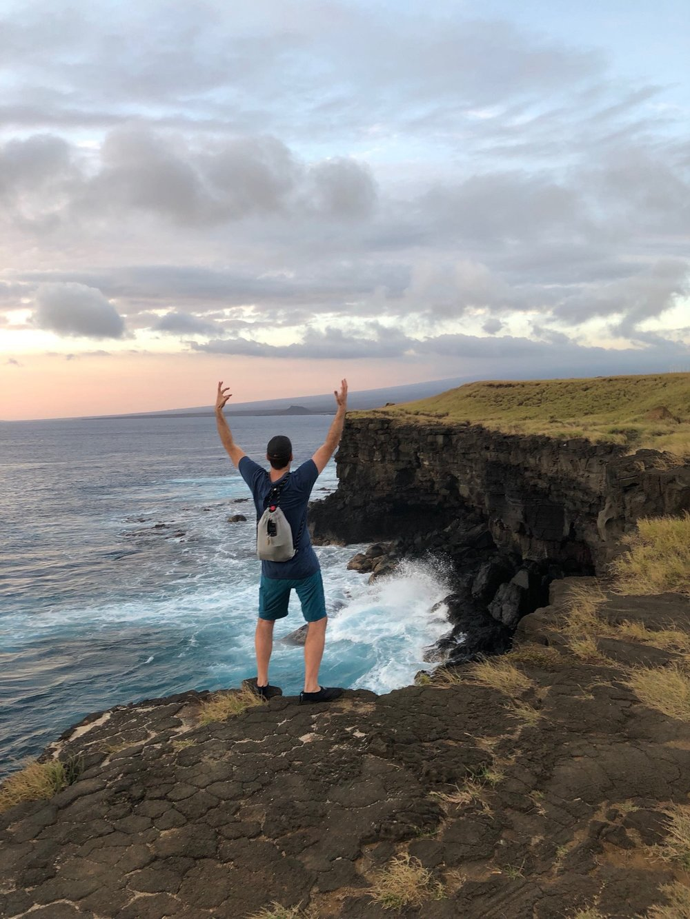Man with hands up at South Point cliffs, Hawaii.