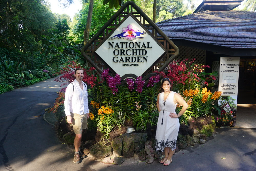 Matt and Kelly stand by the entrance sign to the National Orchid Gardens in Singapore. boldlygotravel.com
