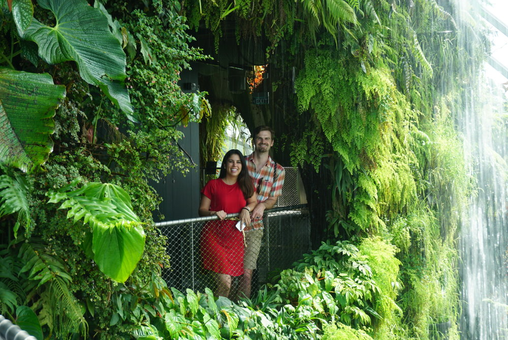 Couple pose for a photo inside a peek through behind the waterfall in the Cloud Forest dome at the Gardens by the Bay in Singapore. boldlygotravel.com