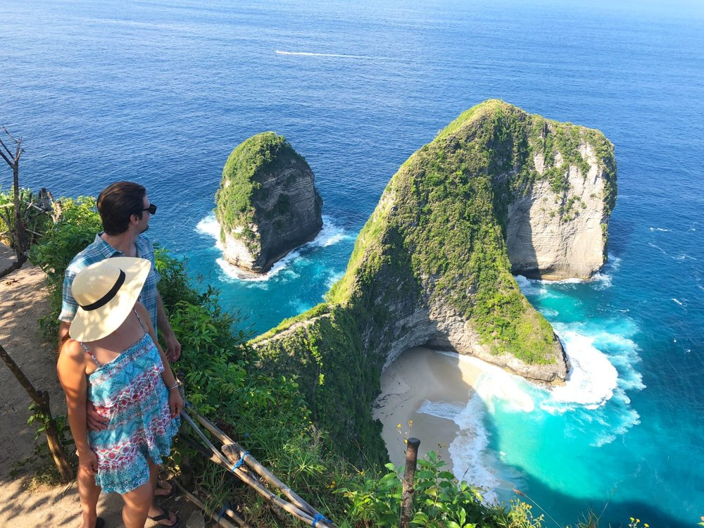 Couple look out at the spectacular Kilingking Bay in Nusa Penida.