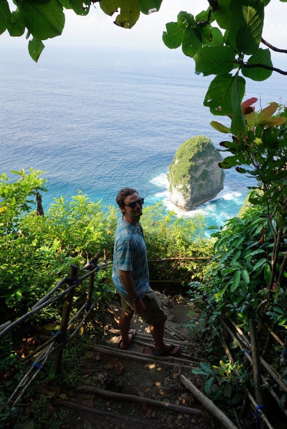 Man stands at lookout for Kilingking Bay in Nusa Penida. boldlygotravel.com