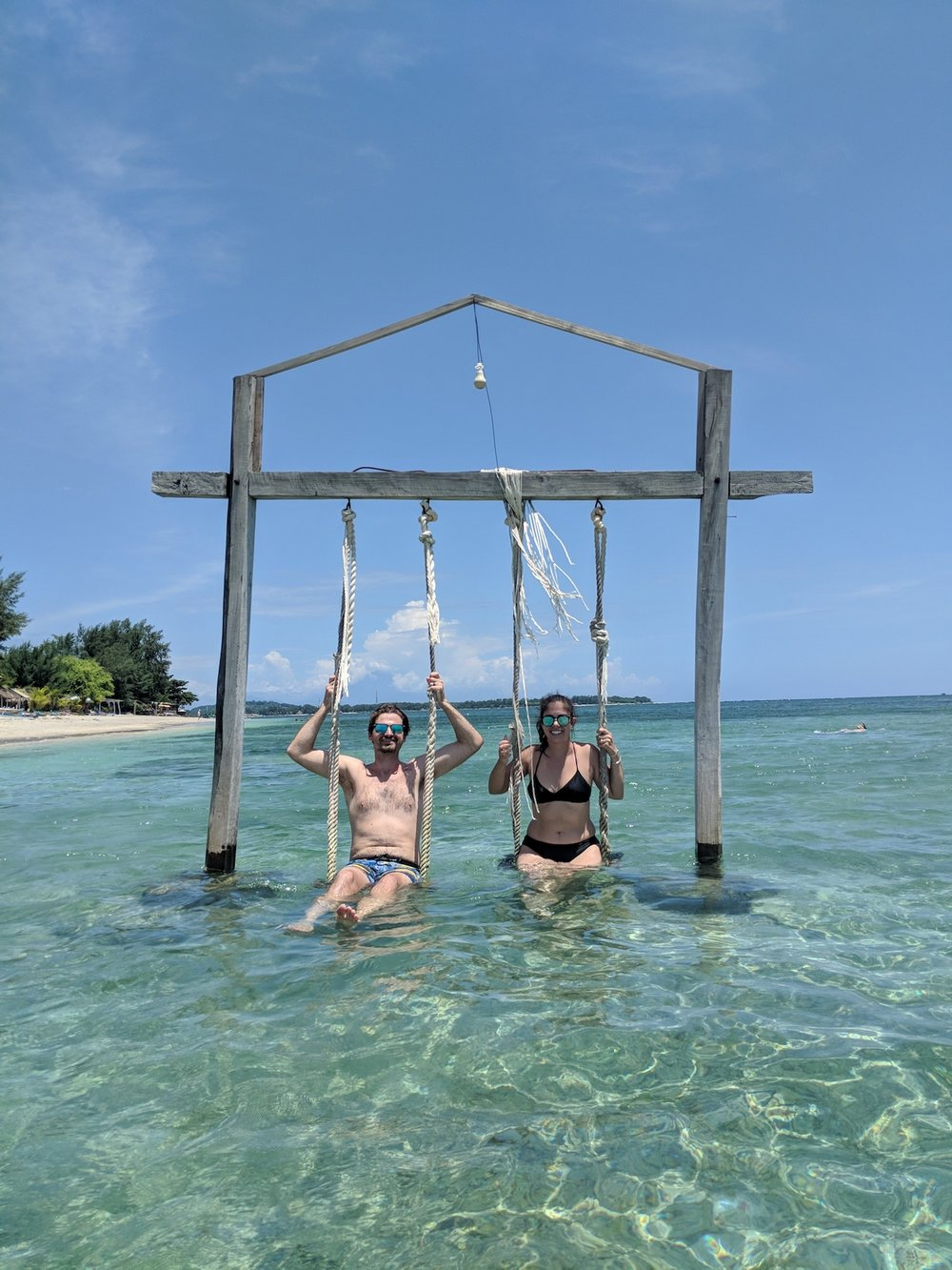 Couple in the lagoon swing on Gili Air, Indonesia. boldlygotravel.com
