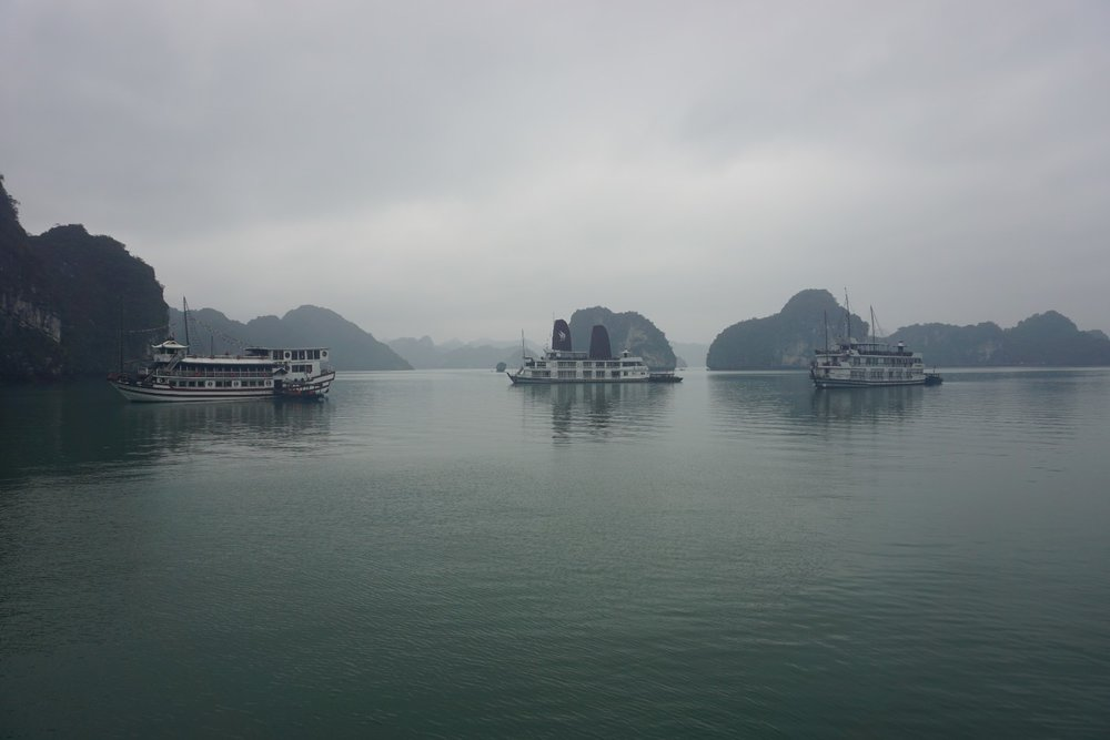boats ferry out to Ha Long Bay (a UNESCO World Heritage Site) for tourist visits in Vietnam. Boldlygotravel.com