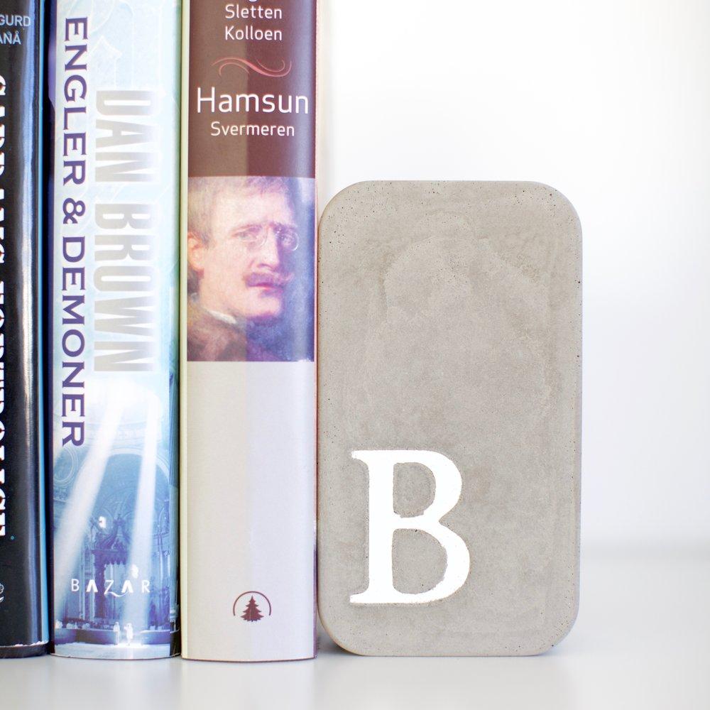 Bokstøtta Stå - Bokstøtta Stå holder orden i hyllene. Med sin tyngde i betong trenger du ikke irritere deg over falne bøker.Høyde ca 14 cmPris kr 180,-
