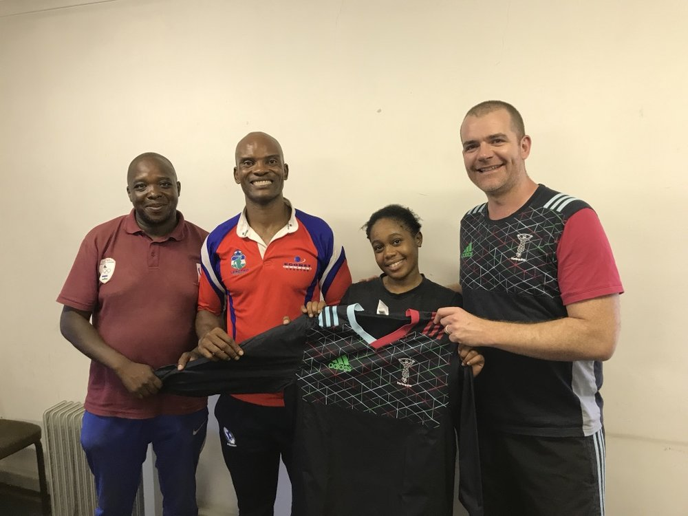 Marc presenting a Harlequins training top to one of our new coaches