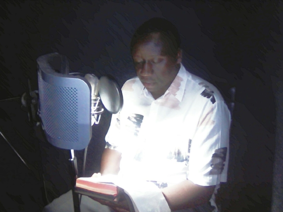 Pastor reading audio Bible in Runyankole-Rukiga