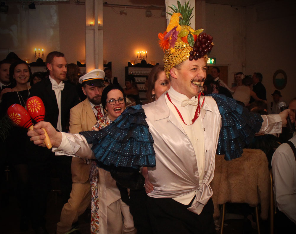 Champagne Charlie leading a conga line with a fruit headdress