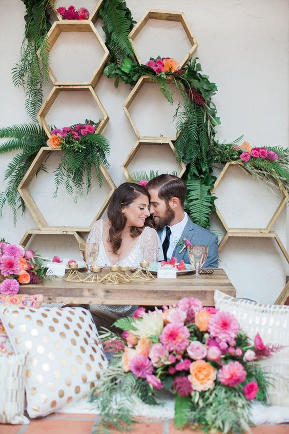 Nothing makes a statement like a stunning backdrop! This photo from mywedding.com with the geo shapes and bright florals are everything!