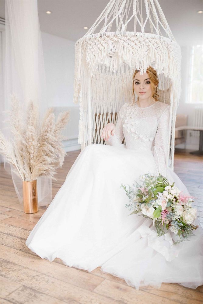 Bride with her bouquet, sitting in a macrame swing at The Old Parish Rooms Essex venue