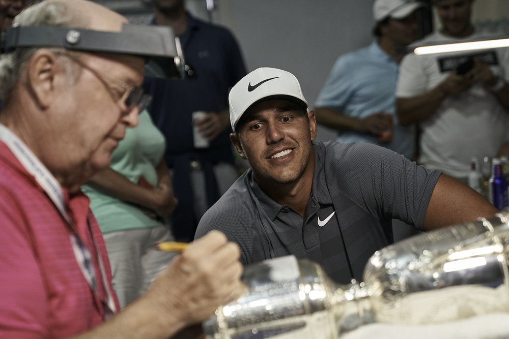 Champion Brooks Koepka watches as his name is engraved on the trophy for the second straight year.   Sony A9, Sony 24-70mm f2.8 GM.  ©USGA/Darren Carroll