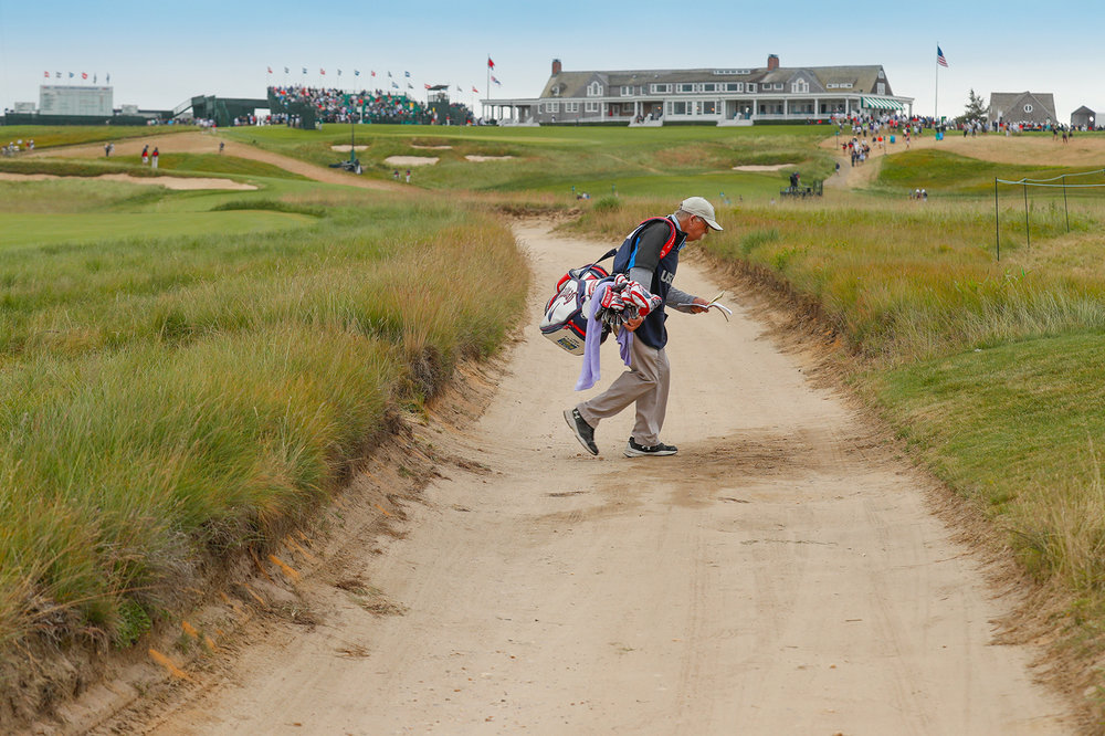 """Mike """"Fluff"""" Cowan, Jim Furyk's caddie, makes his way to the 5th tee during Friday's second round.  Canon EOS 1DX-Mark II, Canon EF 70-200mm f2.8LII  ©USGA/Darren Carroll"""