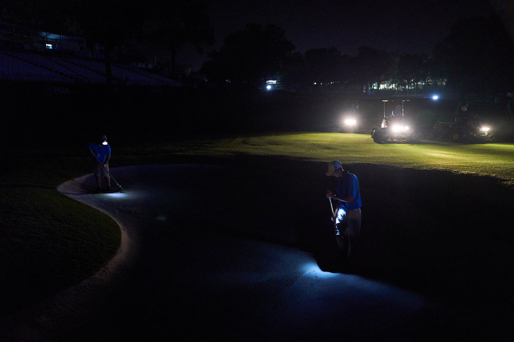 Members of the maintenance staff tend to a bunker at the 18th early in the morning before round two..  (Sony A9, Sony 24-70mm f2.8 G-Master)