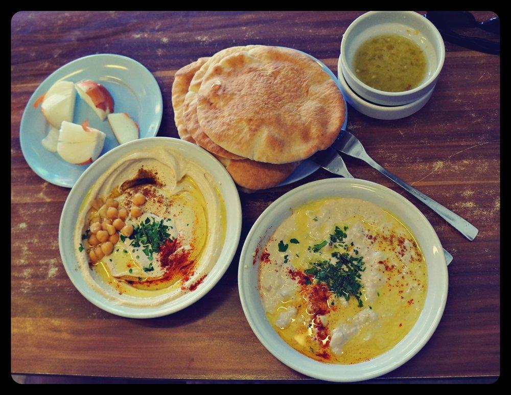Hummus podawany z chlebkiem pita oraz surową cebulą