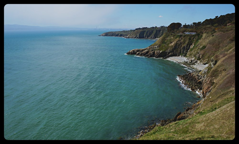 Howth Head's cliffs. The Wicklow mountains and panorama of Dublin can be seen on the horizon.