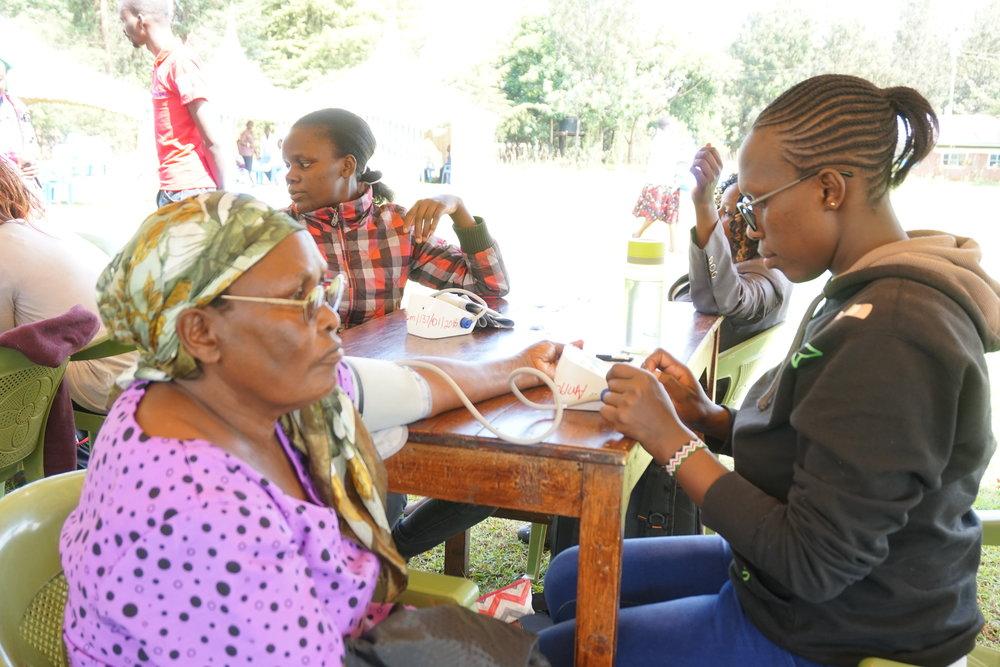 AMPATH staff measure blood pressures at a community screening in Turbo county, Kenya.
