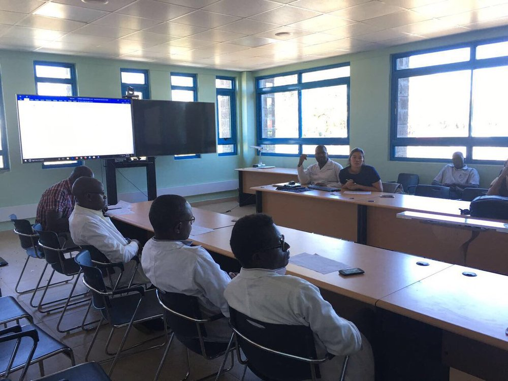 Physicians and medical trainees in Kenya participate in a teleconference with colleagues in Indiana.