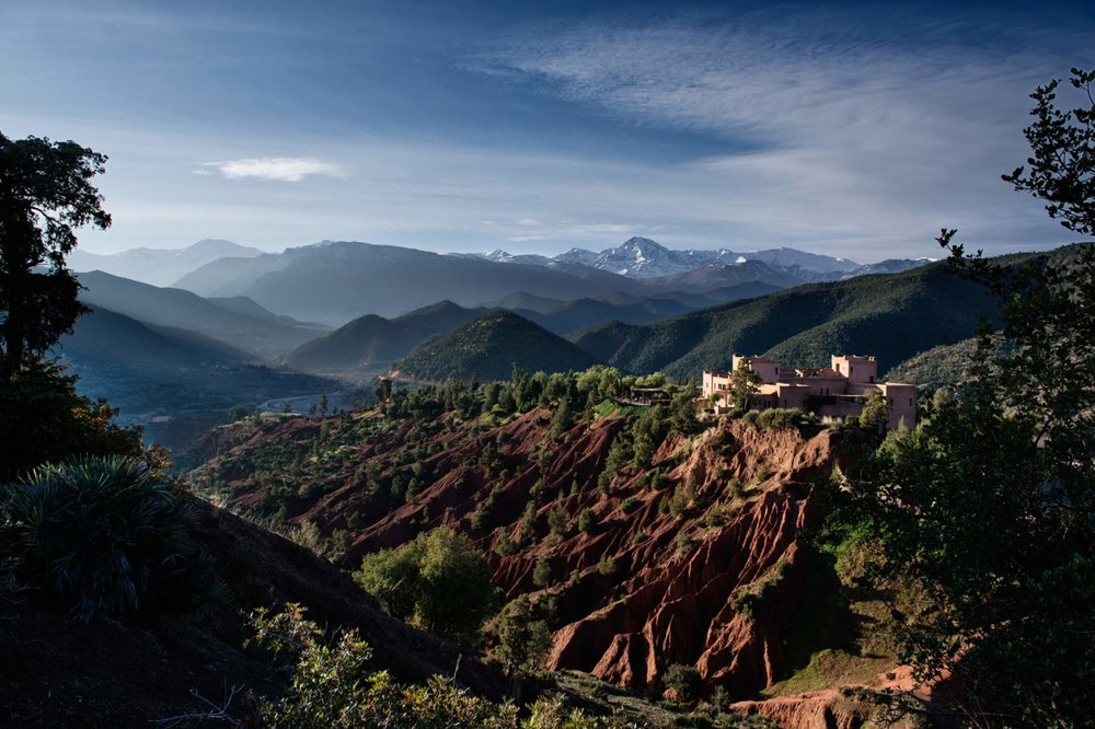 Kasbah Bab Ourika - High up in the Atlas Mountains, the enchanting Kasbah Bab Ourika overlooks a breathtaking landscape. 360 degree panoramic views? Check! From your hilltop lookout at the apex of the Ourika Valley a feast of natural beauty waits to melt your heart. Gaze down to the river and let the olive groves, oranges and lemons lead your eyes on a colourful dance between the green fields all the way up to snowy mountain peaks dazzling in the sunlight.The authentic charm of the Kasbah Bab Ourika makes relaxation easy. Whether you're chilling in your individually decorated room, or unwinding by the secluded swimming pool, get ready to be warmed by the yummy Moroccan sun from dawn till dusk.