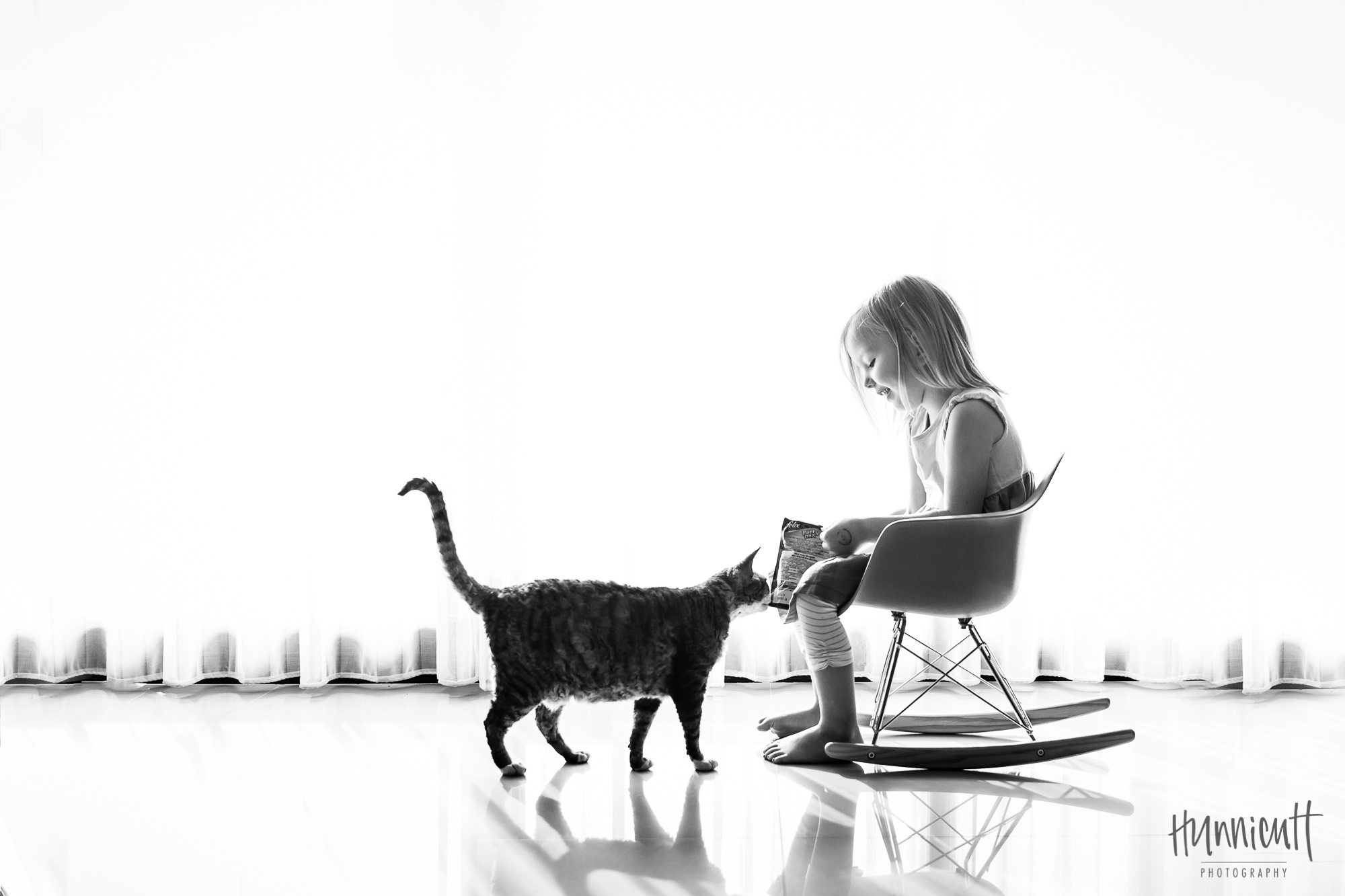 Young_Girl_Sitting_In_Rocking_Chair_Feeding_Cat_Rebecca_Hunnicutt_Farren
