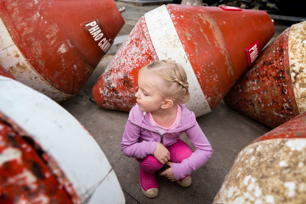 girl_looking_at_orange_buoys_in_vietnam_Personal_portfolio_by_rebecca_hunnicutt_farren.jpg