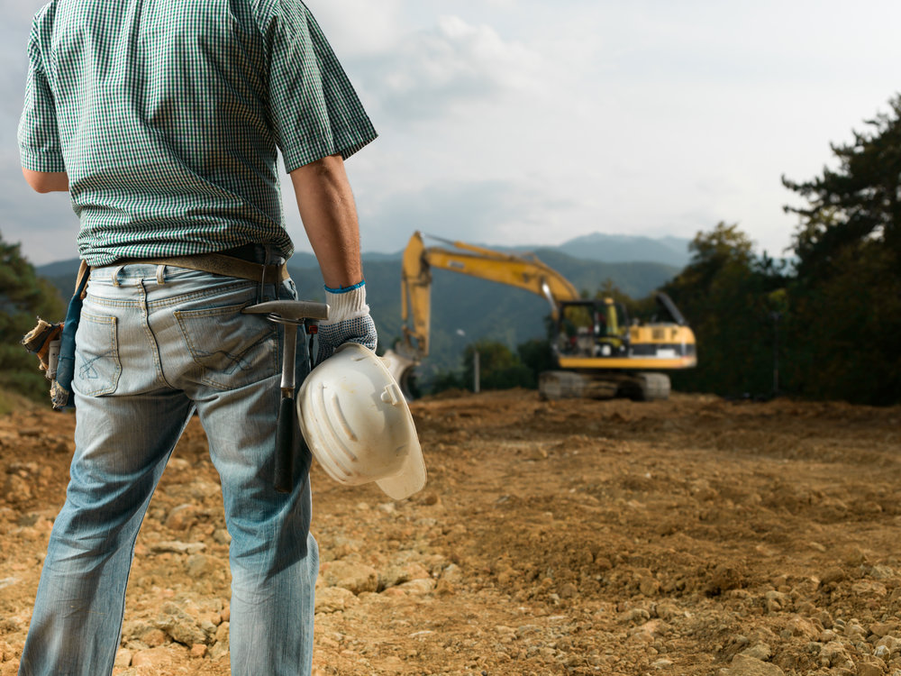 Construction worker holding hard hat in front of an excavator