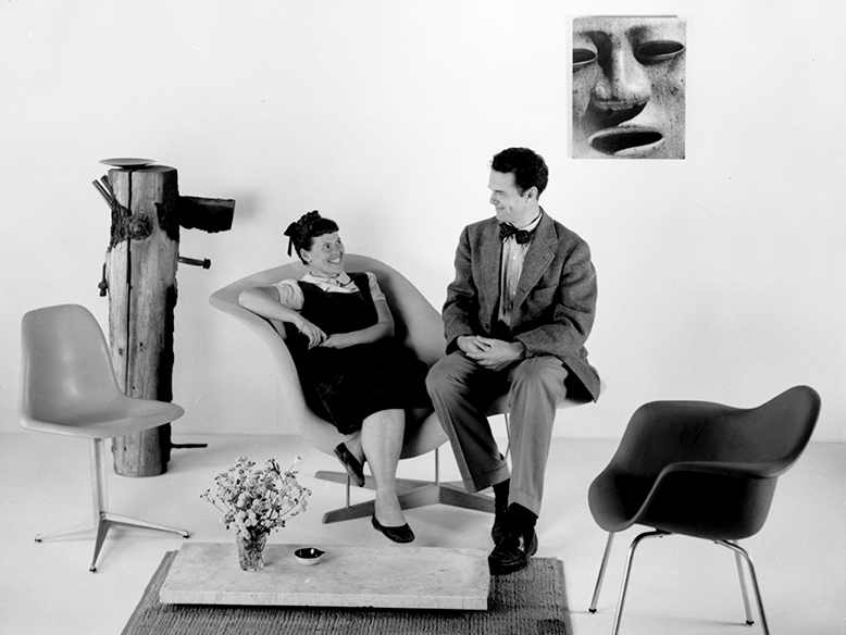 Charles and Ray Eames sitting on the La Chaise Prototype, 1948. ©Eames Office LLC. The World of Charles and Ray Eames is curated and organized by Barbican Art Gallery, London.
