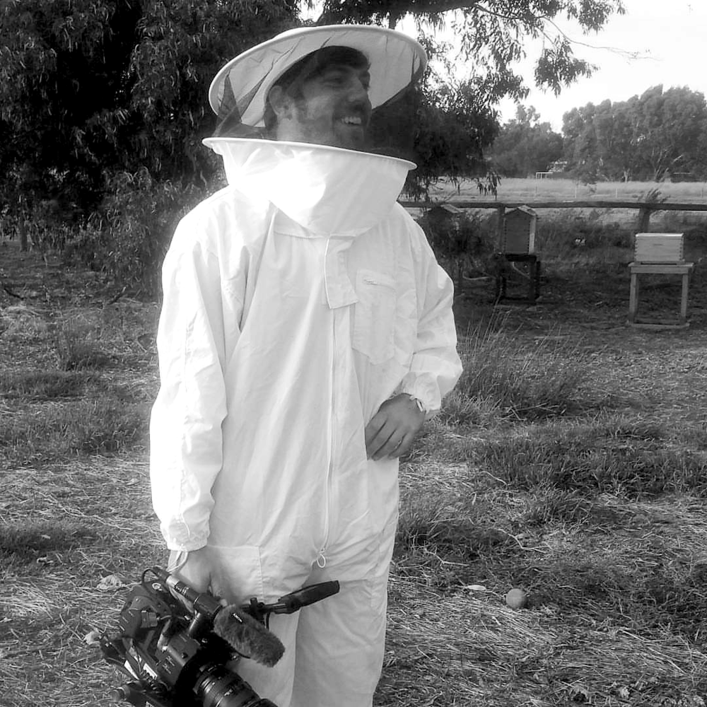 Mitchell in a Beekeeper suit holding a camera