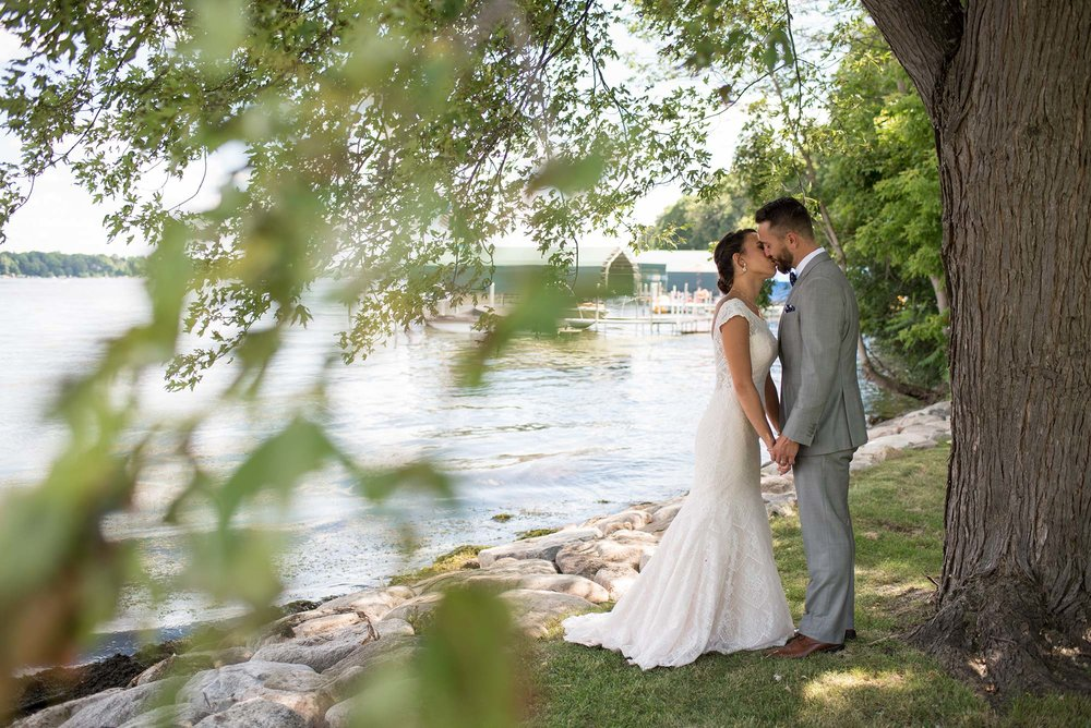 Bride and Groom Kissing by Lake Under a Tree on Wedding Day  |  Life & Art Photography  |  Elopement and Destination Wedding Photographer