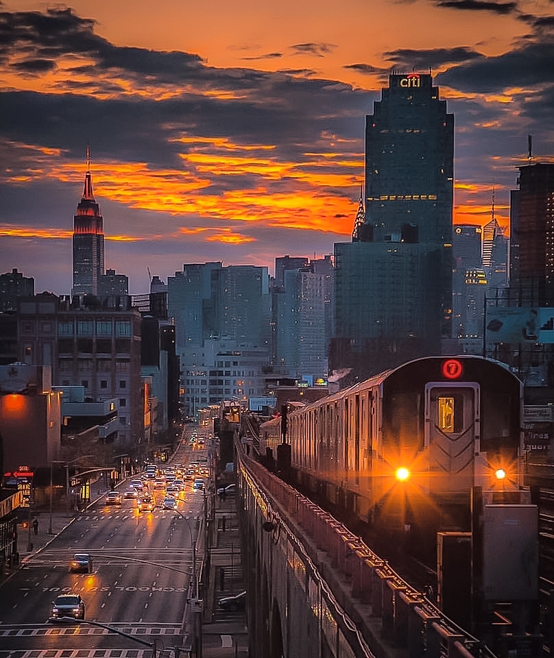 THE LEGENDARY 7 TRAIN IN QUEENS WITNESSING AN EPIC SUNRISE. THE 7 TRAINS TAKES YOU TO SEVERAL PLACES IN QUEENS: LONG ISLAND CITY WATERFRONT, CITI FIELD, U.S. OPEN, FLUSHING-MEADOW PARK, AND THE BILLIE JEAN TENNIS NATIONAL CENTER. TO GO TO ASTORIA, TAKE THE N OR W TRAINS. THIS PHOTO WAS TAKEN FROM 40TH STREET STOP BY LUCAS COMPAN