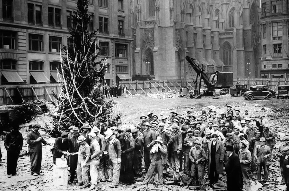 In December 1931, demolition workers at the Rockefeller Center construction site pooled their money together to buy a Christmas tree. The 20-foot high balsam fir was decorated with handmade garlands by the men's families. This photo, taken on Christmas Eve, shows the men lined up to receive their wages. [ 20 feet (6.1 meters) tall, origin not on record]
