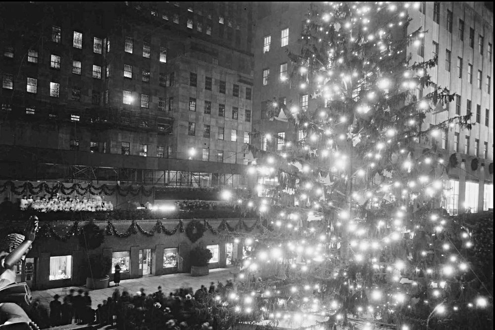 Rockefeller Center decided to make the Christmas Tree an annual tradition and held the very first tree lighting ceremony. [50 feet (15 meters) tall, origin not on record]. Image:NYPL