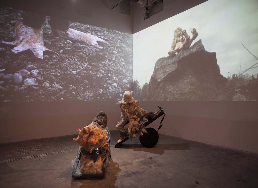 Becoming Beast , Installation view, NURTUREart, HD Three-channel video projection, 17:00, with sculptural models  GM invertus: papier-mâché, wax raw wool, felt, wood, wire mesh, found objects, 26 x 20 x 29 in/66.04 x 50.8 x 73.66 cm  Mono-handler: papier-mâché, wax, raw wool, felt, wood, branches, found objects, 38 x 13 x 37 in/96.52 x 33.02 x 93.98 cm