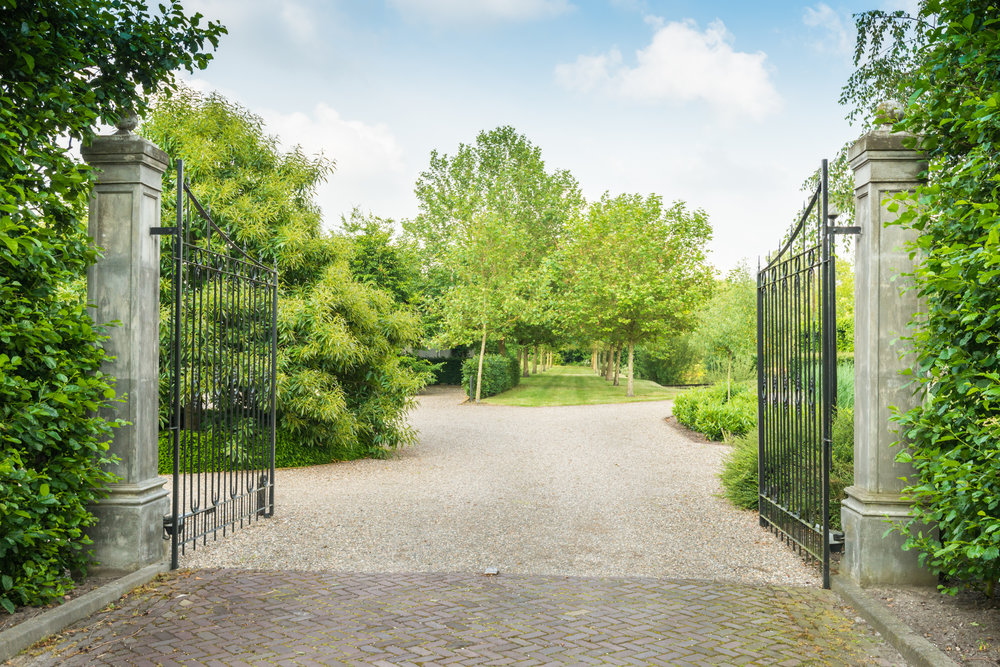 Opened black wrought iron gate of a large estate