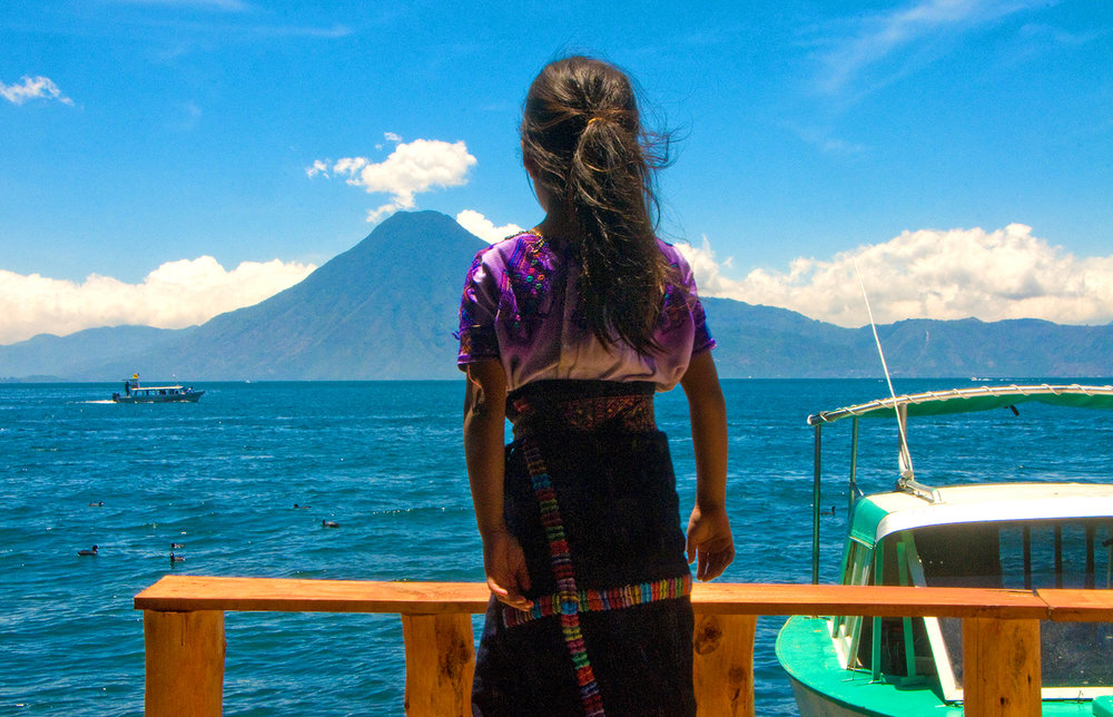A young Guatemalan girl soaks in the sights at Lake Atitlan, Guatemala. The lake is surrounded by a ring of volcanoes and is flanked by a scattering of indigenous Mayan communities, which makes it one of the most authentically rich and visually stunning attractions in the entire country.